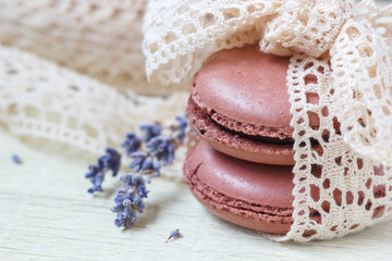 pastel colored macaroon with vintage lace ribbon bow and lavender on paper background