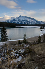 Snow covered mountains in Banff with ice-rimmed lake in foreground