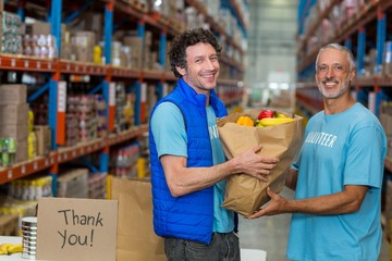 Happy volunteers holding a grocery bag and looking the camera
