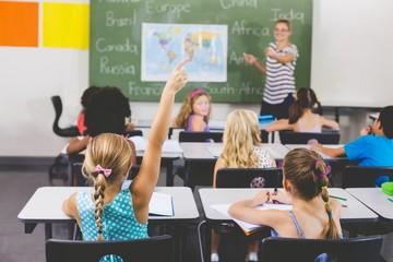 School girl raising hand in classroom