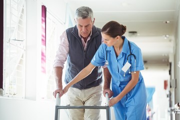 Nurse helping senior man with walking aid