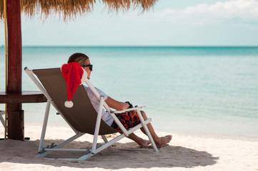 Young man sitting in sunbed at the beach celebrating christmas