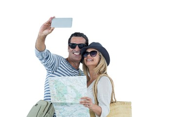 Happy couple with map taking selfie