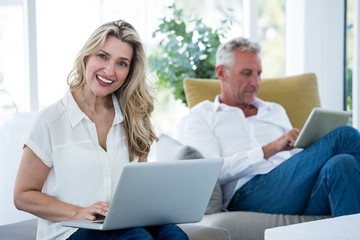 Smiling woman with laptop by man using tablet