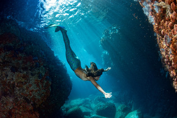Mermaid swimming underwater in the deep blue sea