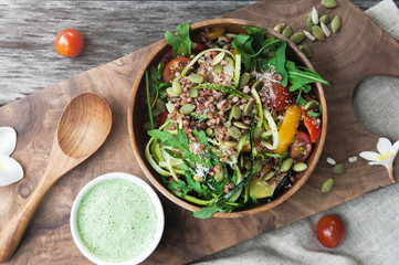 Salad with quinoa, zucchini and arugula in wooden bowl on the wooden board. View from above