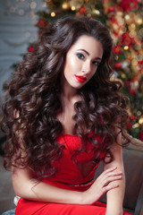 Christmas portrait of a beautiful woman with chic curls in a red dress on a background of the Christmas tree.
