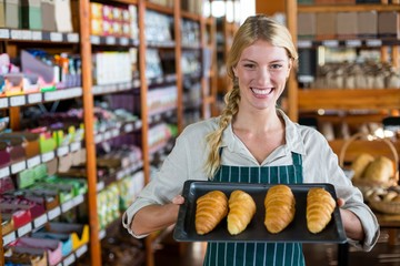 Smiling female staff holding tray of croissants in supermarket