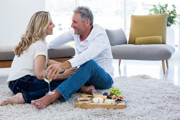 Romantic couple with white wine and food while sitting on rug