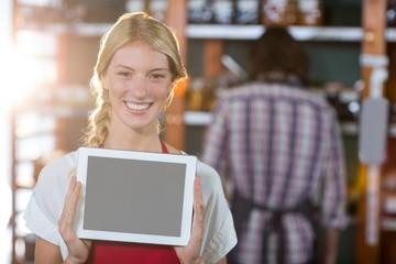 Smiling female staff showing digital tablet in supermarket