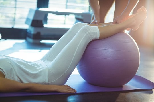 Physiotherapist assisting a patient with exercise ball