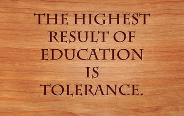 The highest result of education is tolerance - quote by Helen Keller on wooden red oak background