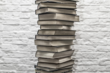 A stack of old books on the background of brick wall