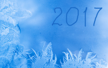 Beautiful New Year winter background (frozen window as a winter background with 2017 written on it)