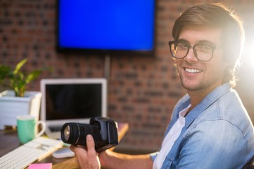 Portrait of smiling man holding camera