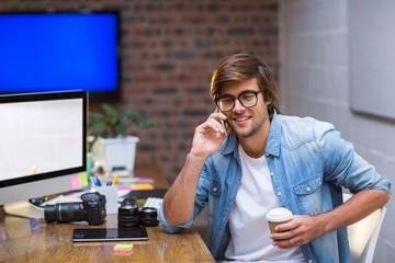 Young man talking on mobile phone in office