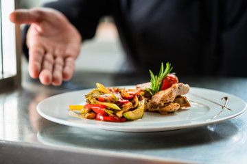 Koch zeigt stolz das von ihm gekochte Essen oder Gericht auf Anrichte in Restaurant Küche