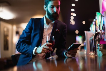 Businessman using mobile phone with glass of red wine in hand