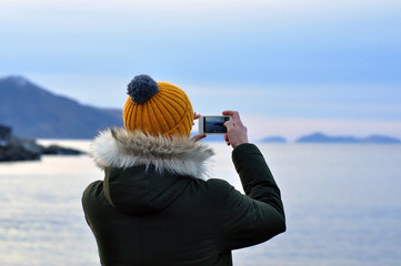 A man taking a picture by phone in Oslo during a cold gray winter Day