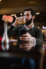 Man holding mobile phone and having a drink