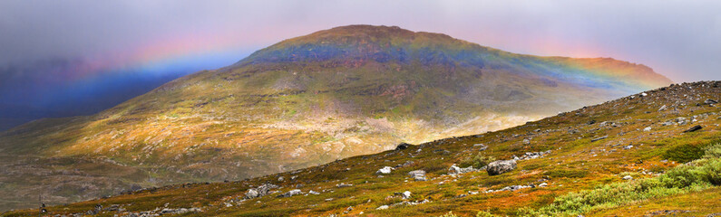 Wide rainbow over mountain ranges Sarek national Park Sweden.