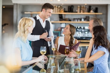 Waiter taking the order from a businessman and his colleagues