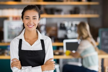 Portrait of smiling waitress standing with arms crossed