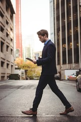 Businessman using digital tablet while crossing the street