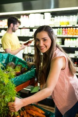 Woman shopping for fresh vegetables in supermarket