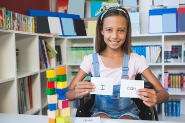 Disabled girl showing placard that reads I Can in library