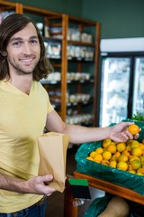 Portrait of smiling man selecting oranges in organic section
