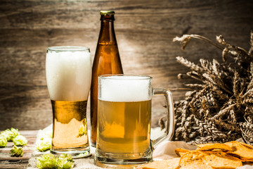 Beer mugs, glasse, bottle on table with chips hops, wheat