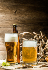 Mug, glasse, bottle of beer with foam on blank wooden background