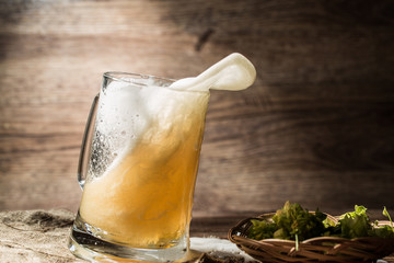 Frothy beer poured from tankard standing on linen cloth
