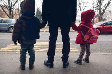 Father with children waiting for the school bus