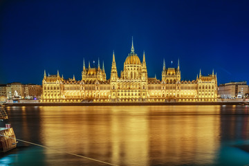 Budapest Parliament building at night on the Danube river in Hungary.