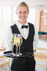 Portrait of waiter holding glasses of champagne