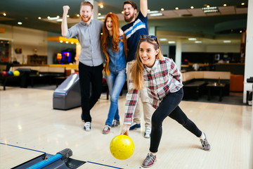 Friends having great time playing bowling