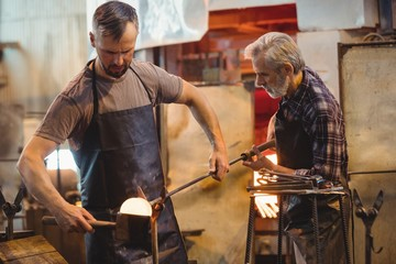 Team of glassblower forming and shaping a molten glass