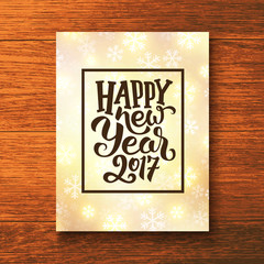 Happy New Year 2017 lettering text in frame on glowing winter background. Vector greeting card template with typography for holidays above wooden backdrop.