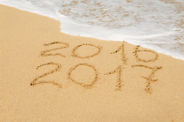 digits  2016 and 2017 on the sand