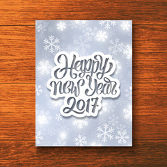 Happy New Year 2017 hand lettering text on paper label over glowing winter background. Vector greeting card template with typography for holidays above wooden backdrop.