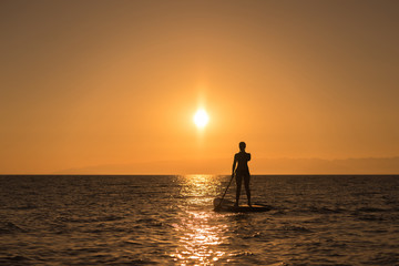 woman silhouette at paddle board in sunset