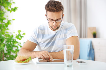 Young man having snack while working with tablet computer in kitchen