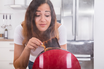Woman Taking Burnt Toast Out Of The Toaster