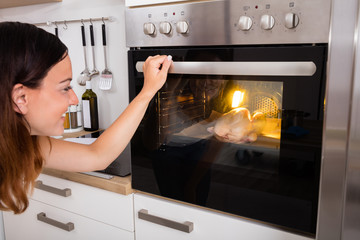 Woman Roasting Chicken Meat In Oven