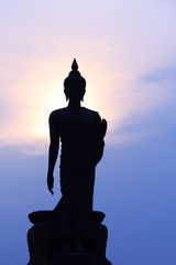 Silhouette of standing Buddha Statue against dramatic sky