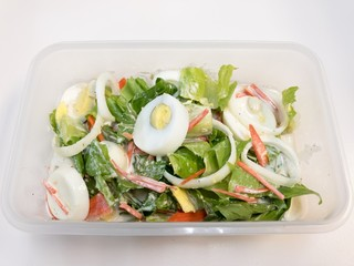 Caesar salad with boiled eggs, carrot, tomato, costa vegetables, and onion in a box.