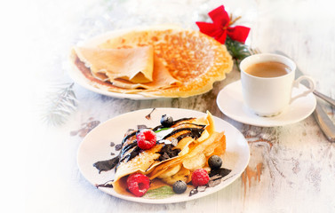 Christmas breakfast. Cup of Coffee and Crepes with fresh berries