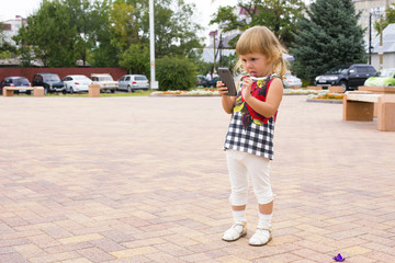Little girl looking mobile phone.